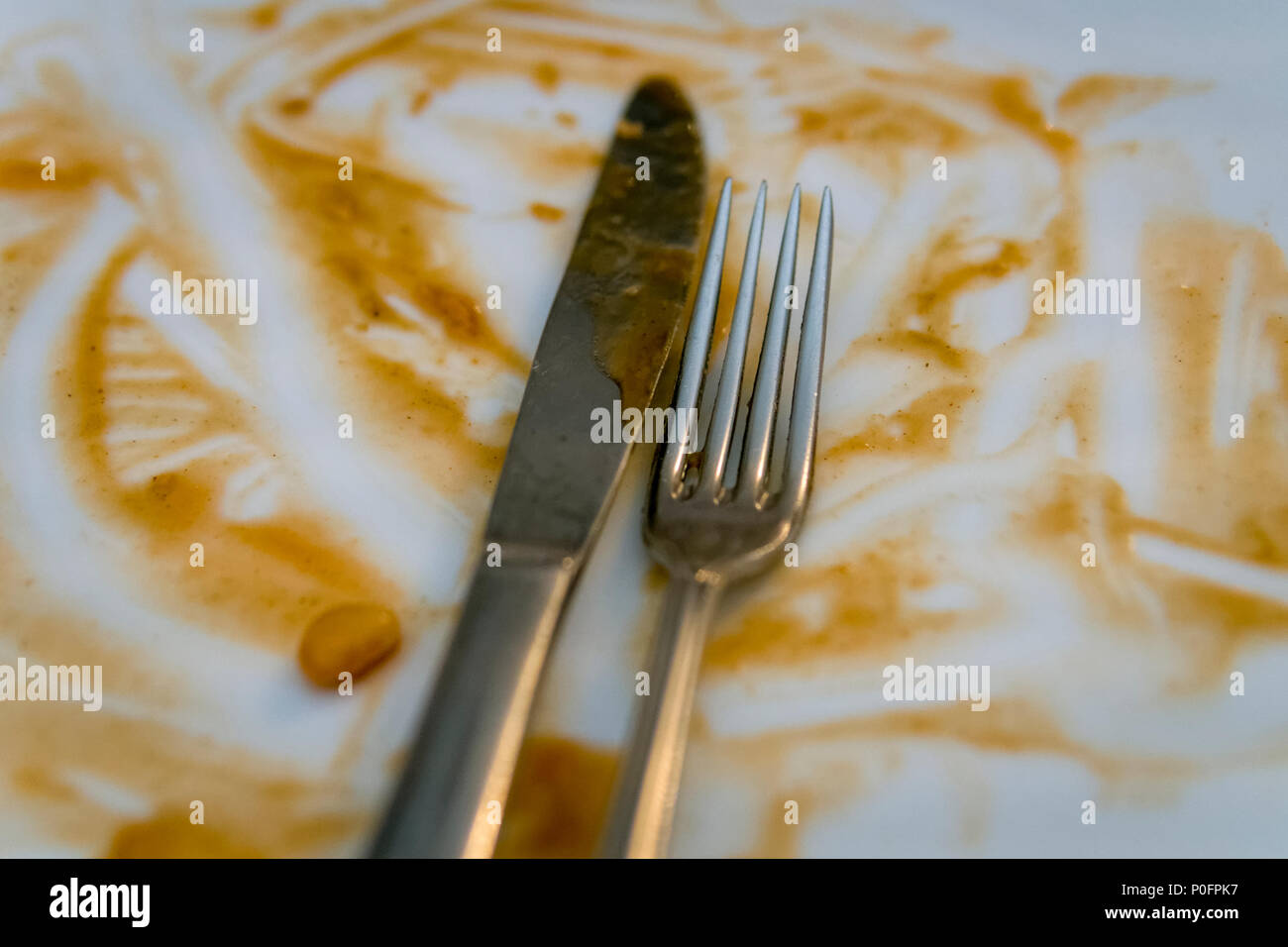 Knife and Fork on plate with leftover food - Stock Image