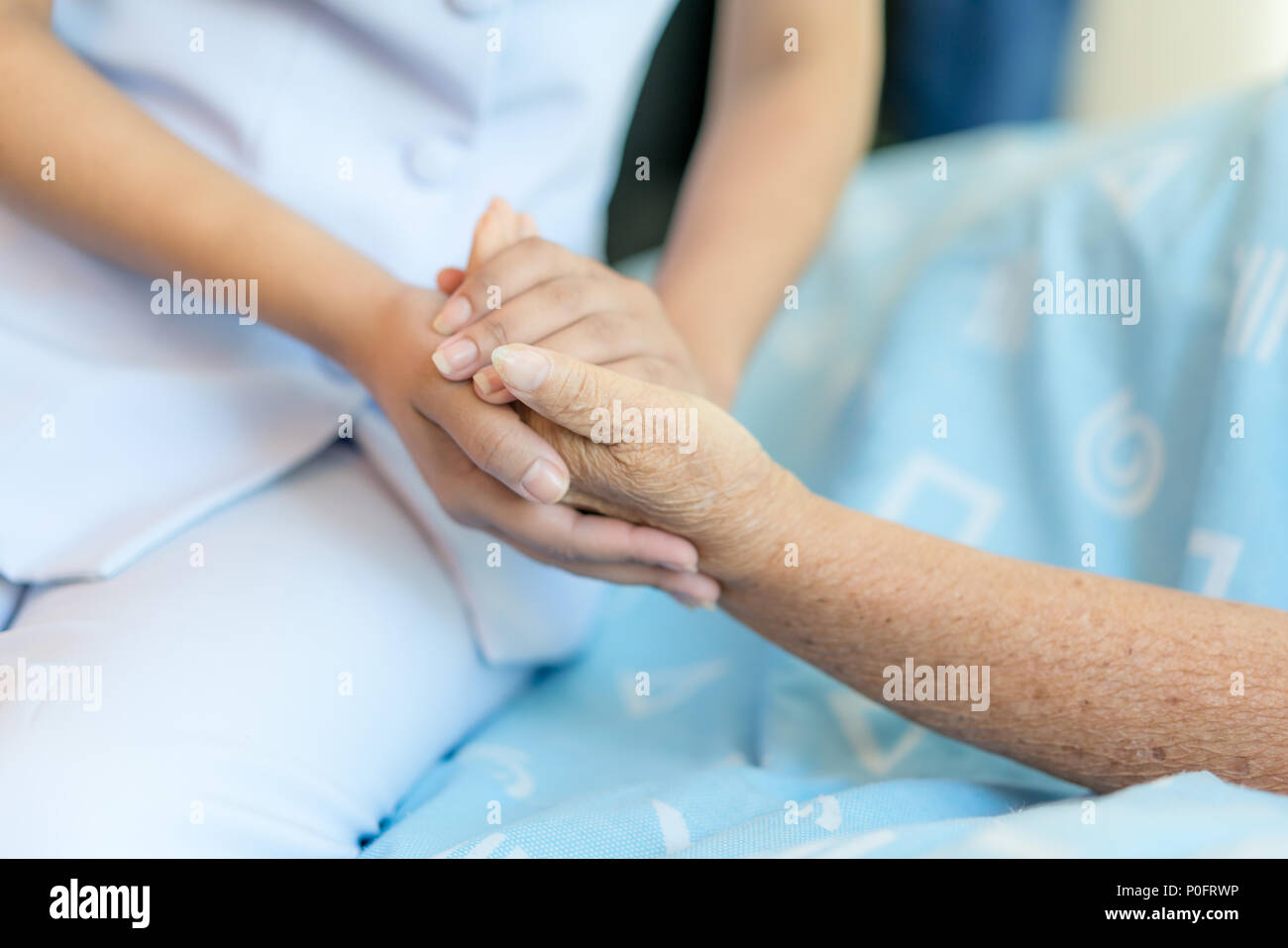 Nurse sitting on a hospital bed next to an older woman helping hands, care for the elderly concept - Stock Image