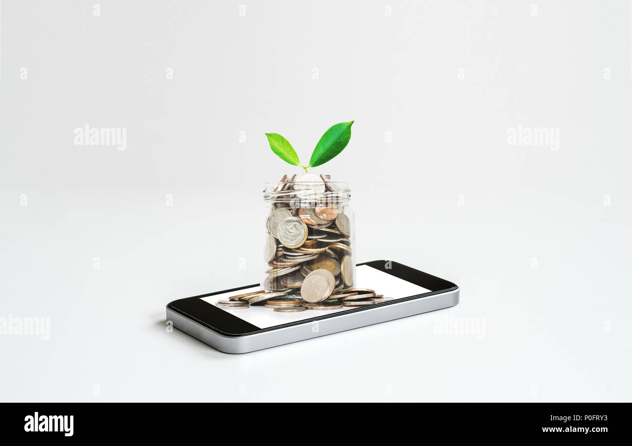 Online banking and making money by online business and e-commerce. Mobile phone and glass jar full of coins - Stock Image