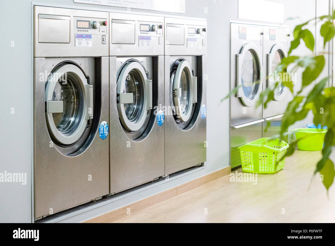 Public laundry with modern, silver washing machines in a row - Stock Image