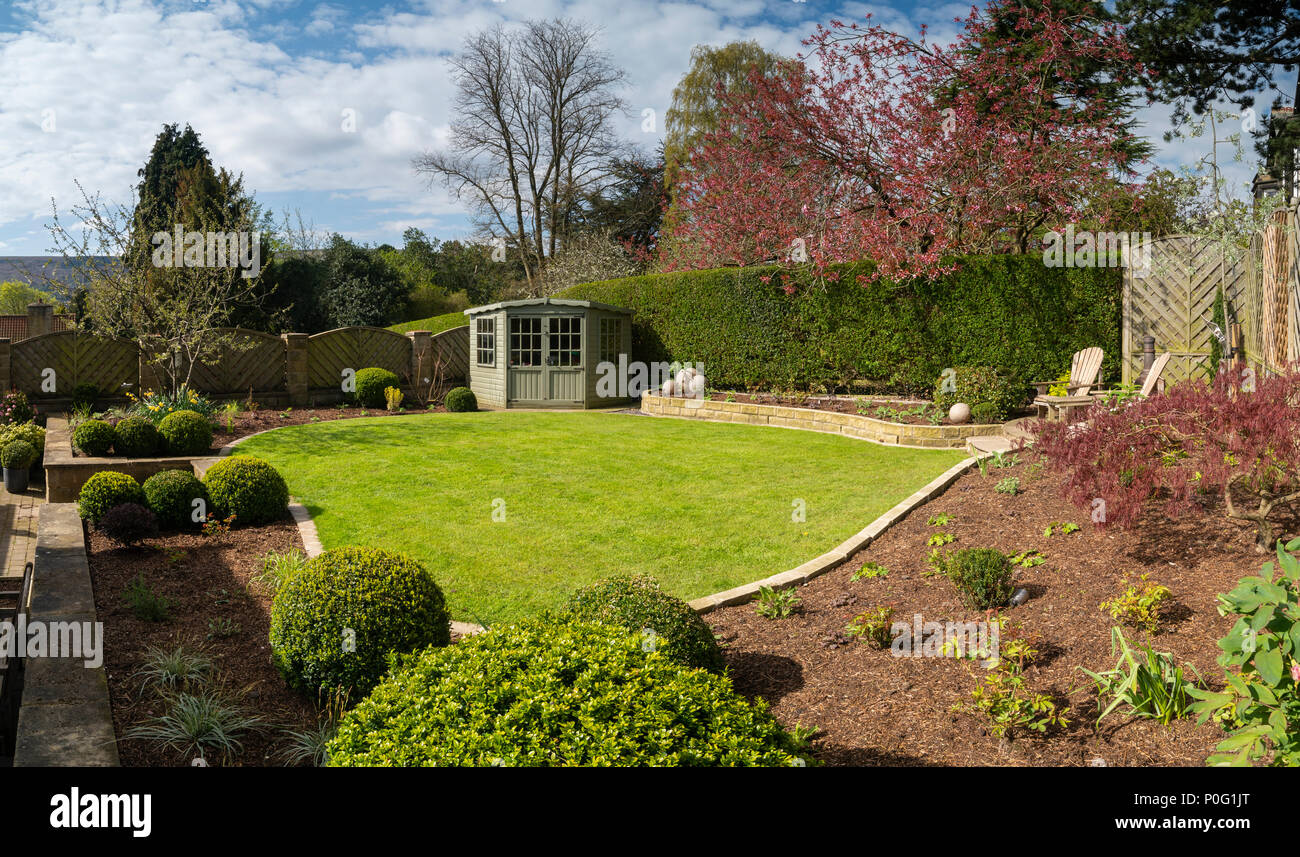 Beautiful, sunny, newly landscaped, private garden with contemporary design, border plants, patio seating, lawn & summerhouse - Yorkshire, England, UK Stock Photo
