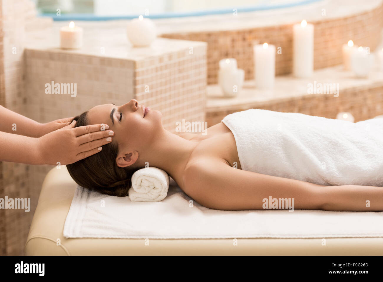 attractive woman relaxing and having head massage in massage salon - Stock Image
