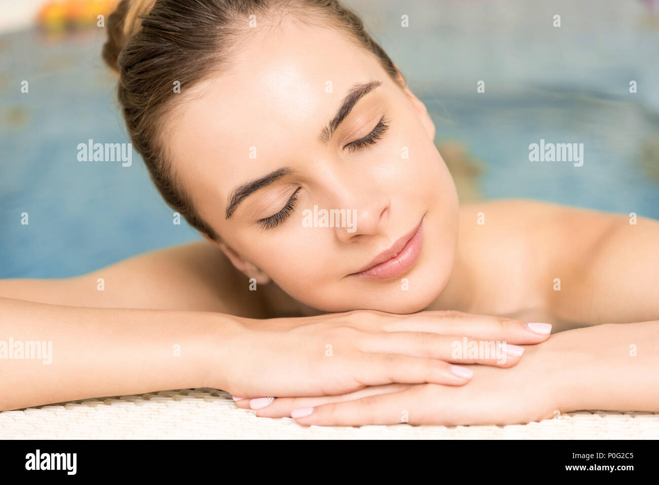 attractive smiling woman with closed eyes relaxing on spa procedure - Stock Image