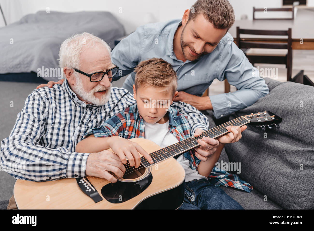 Young boy trying to learn playing guitar while his father and grandpa are helping him - Stock Image