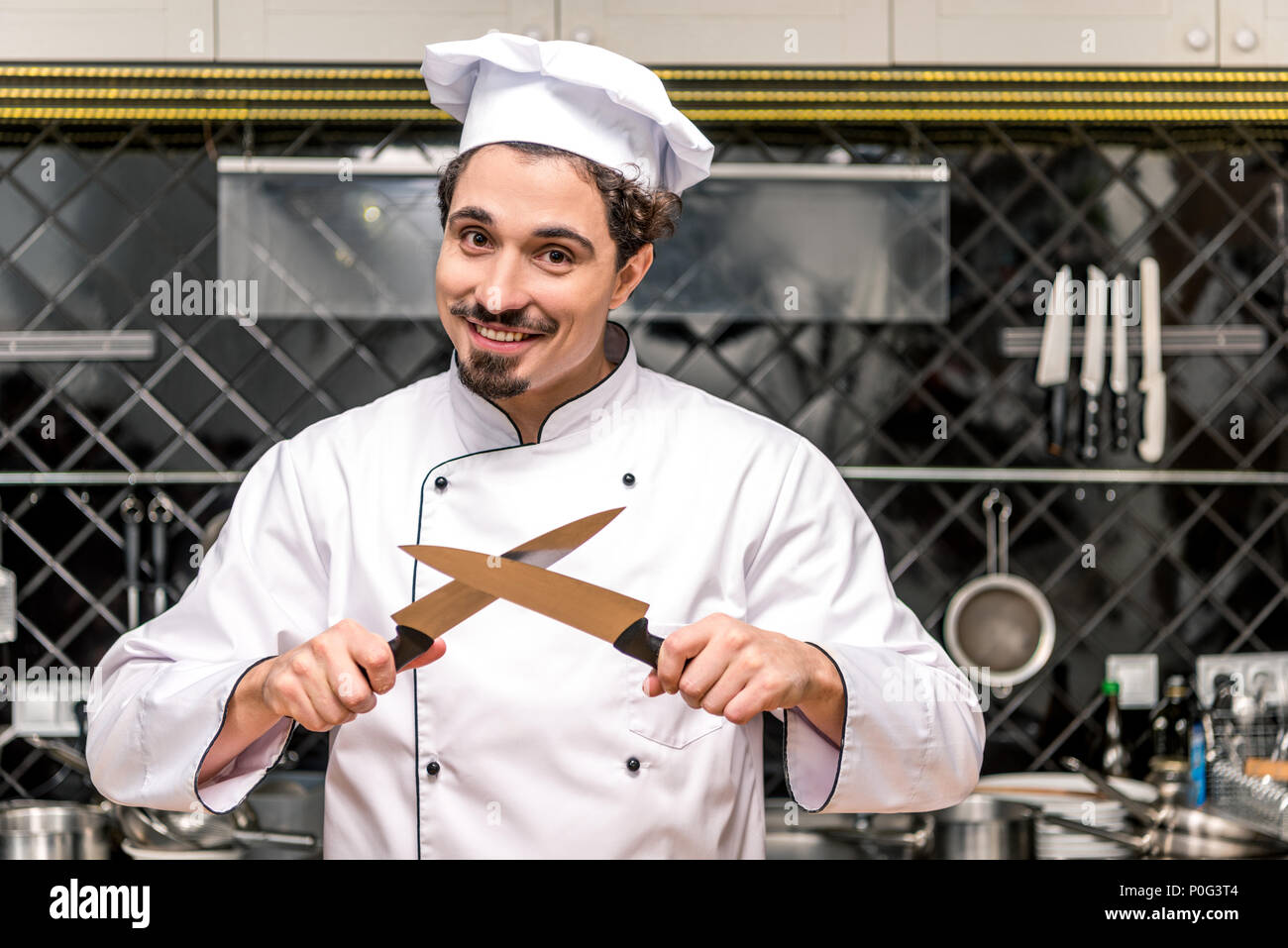 smiling chef standing with crossed knifes - Stock Image
