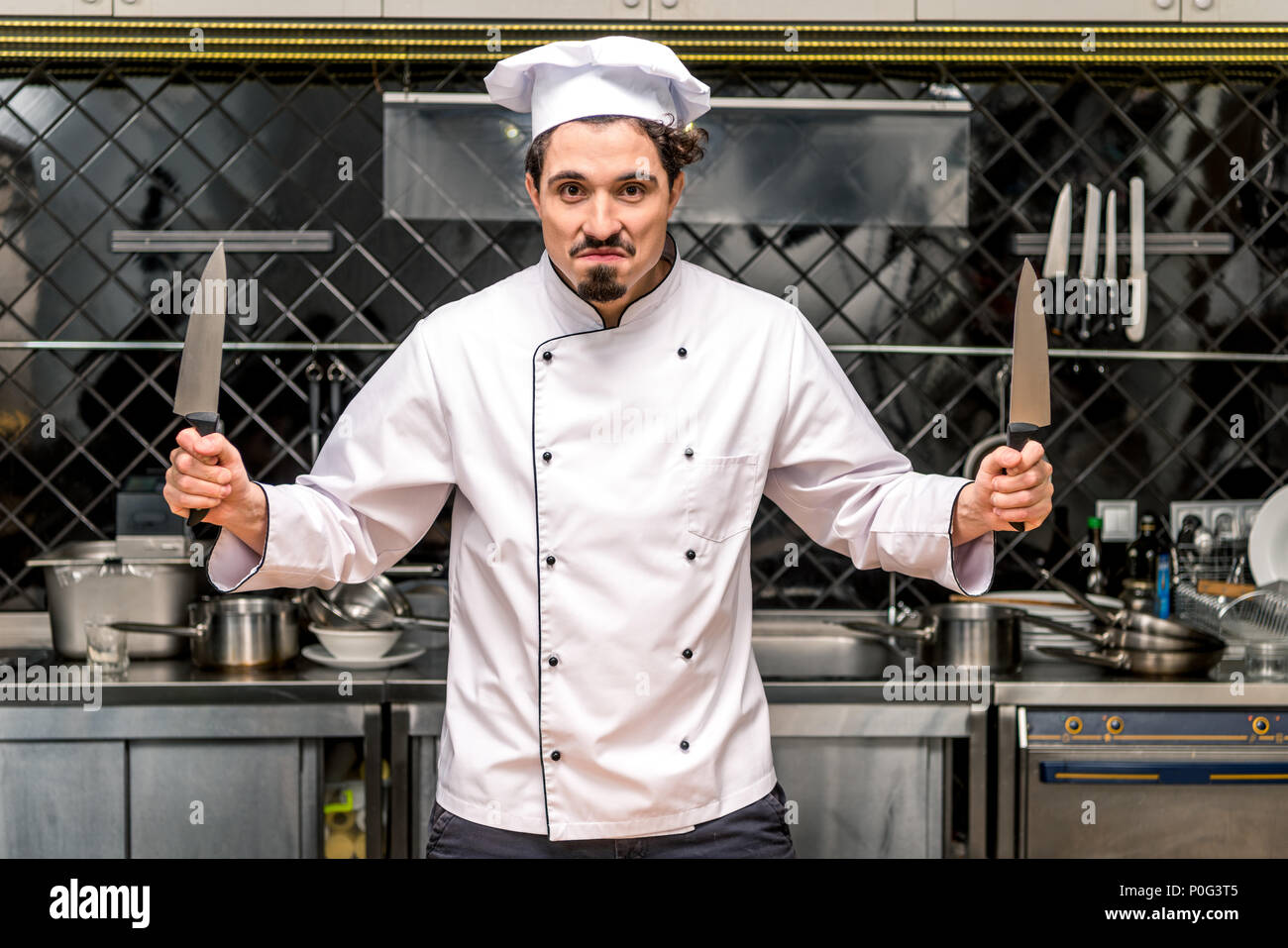 young chef grimacing and holding knifes - Stock Image