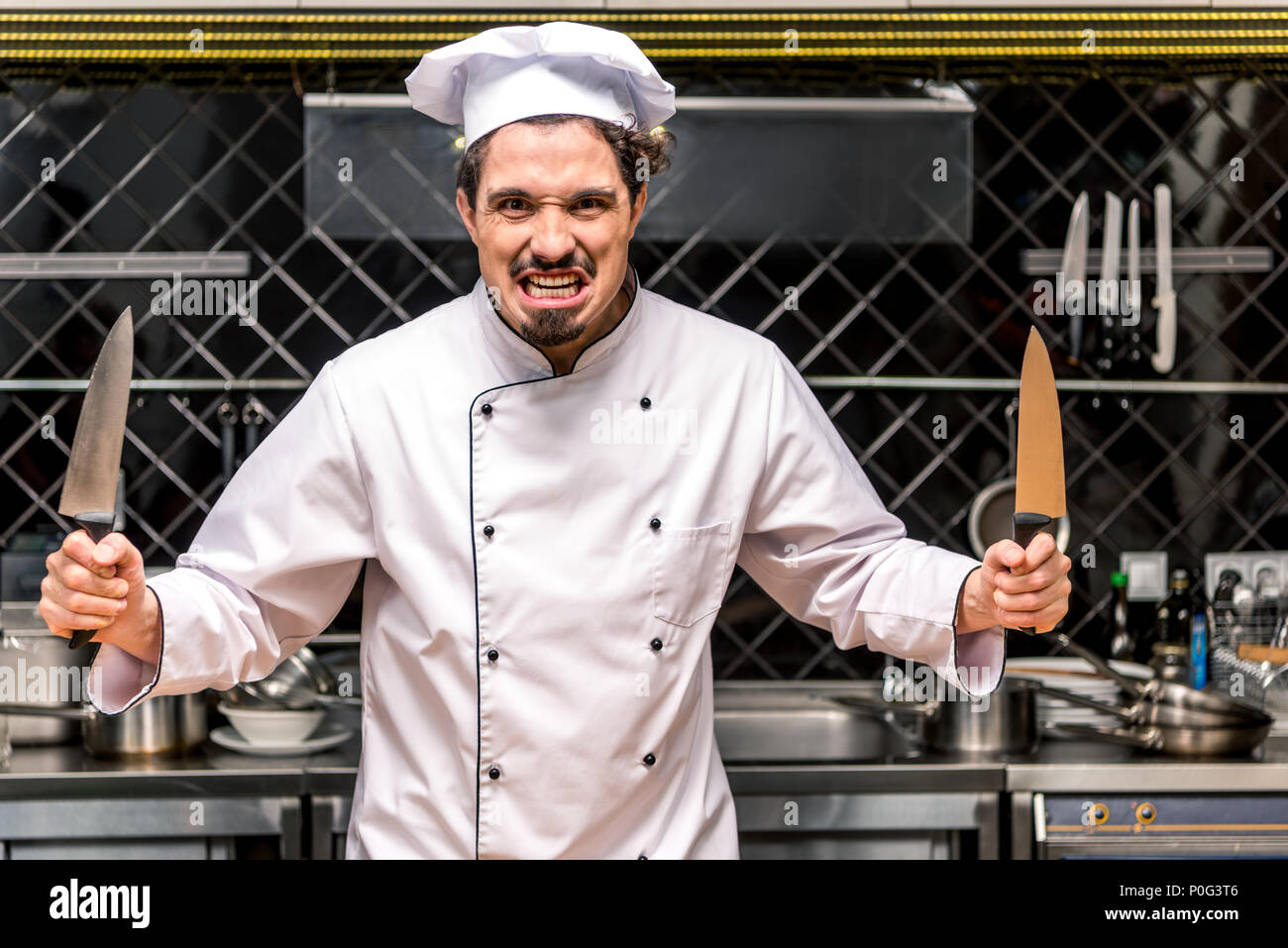 chef grimacing and holding two knifes in hands - Stock Image