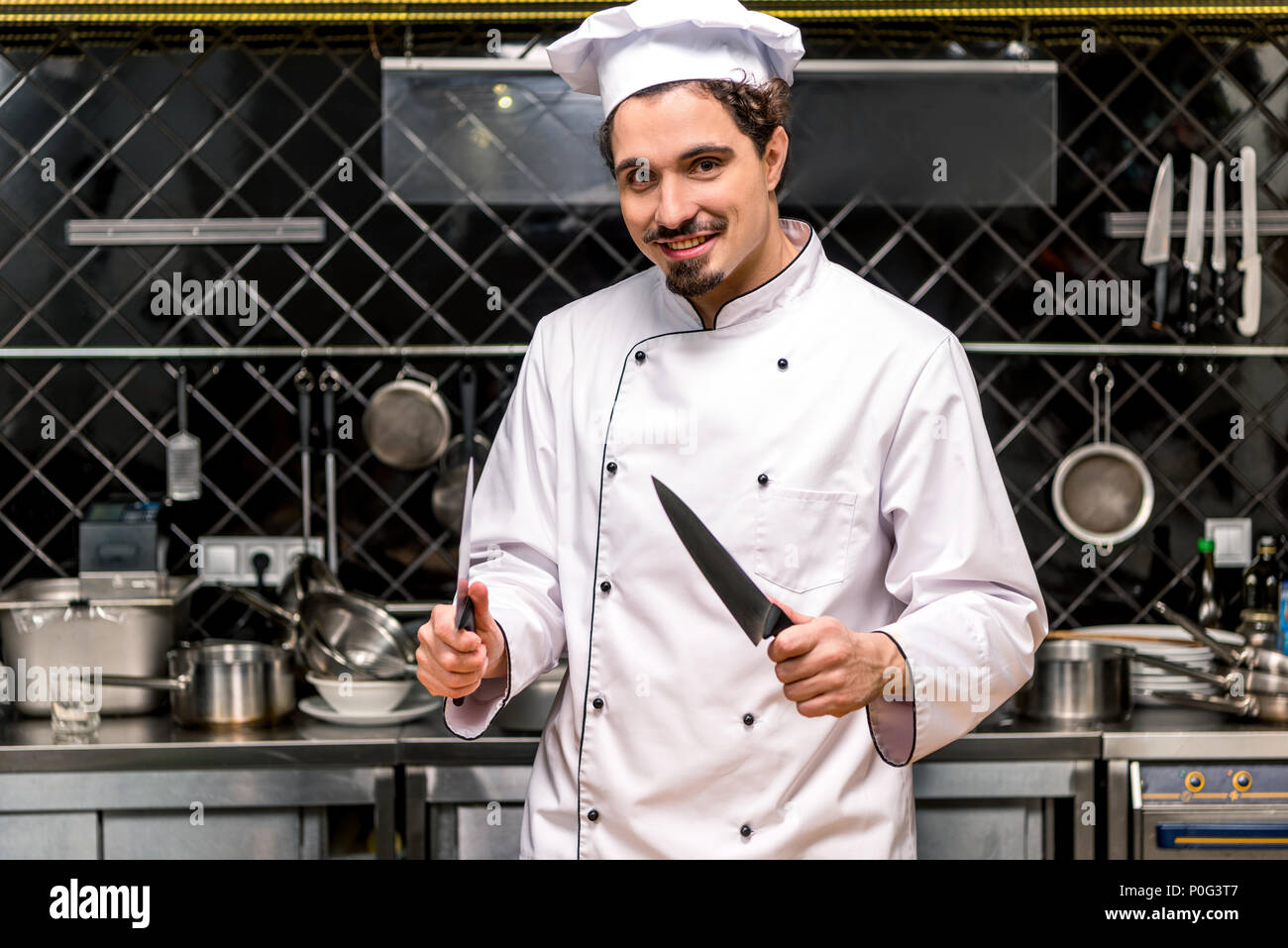 smiling chef standing with knifes in kitchen - Stock Image
