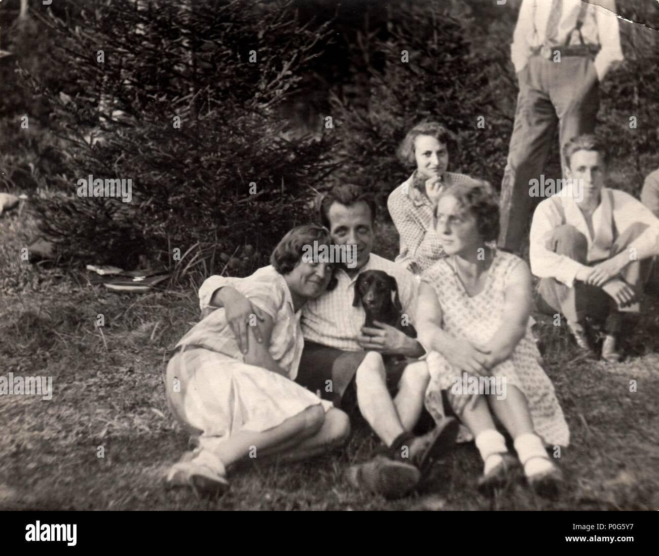 HODONIN, THE CZECHOSLOVAK REPUBLIC, CIRCA 1940: Retro photo shows a young boy with girls. Vintage photo, circa 1940. - Stock Image