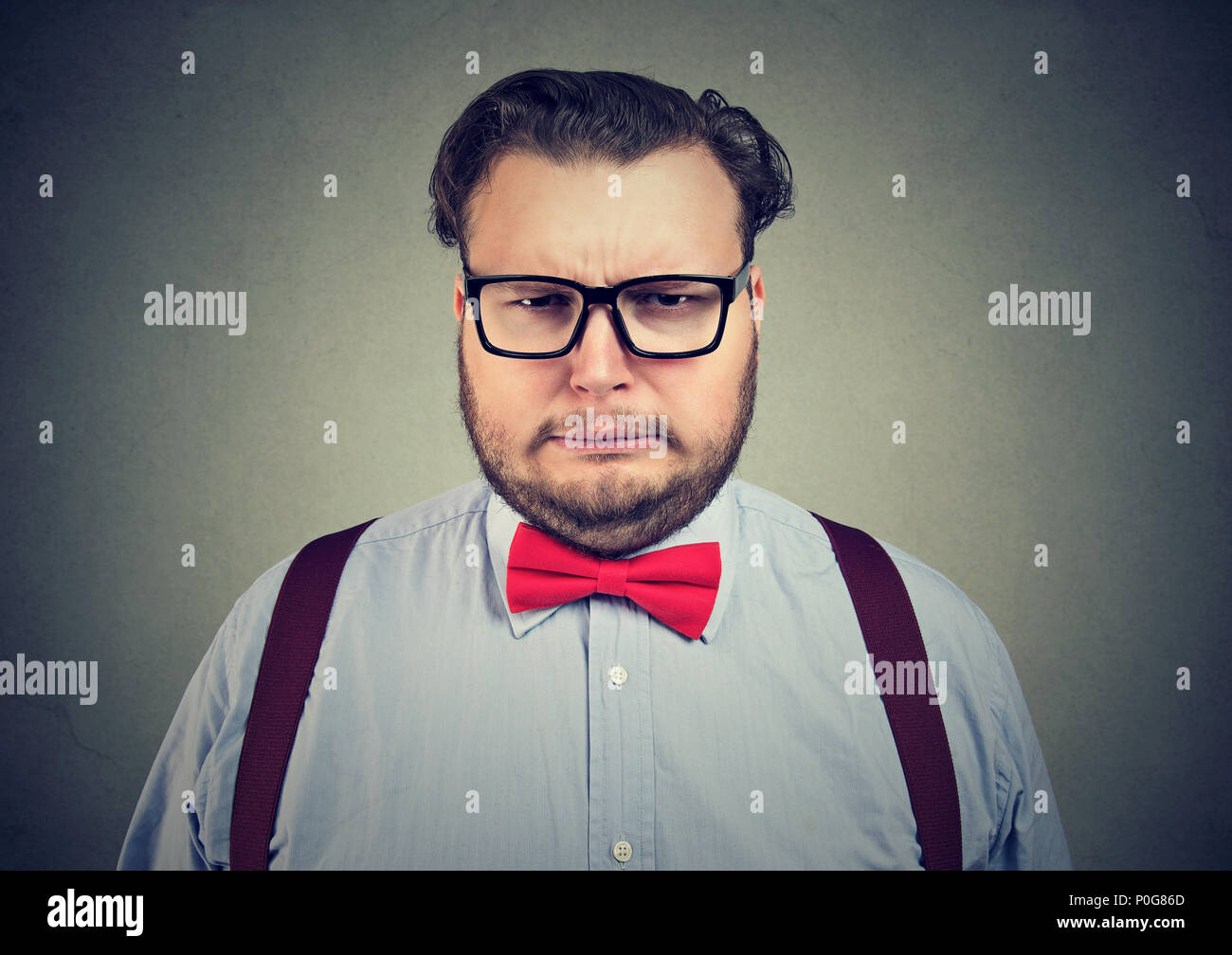 Overweight formal man wearing glasses and making complaining expression of face looking at camera on gray - Stock Image