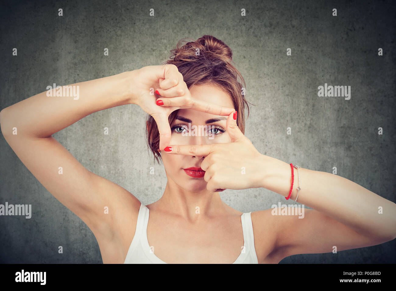 Young girl making frame with fingers and looking through limits at camera on gray background - Stock Image