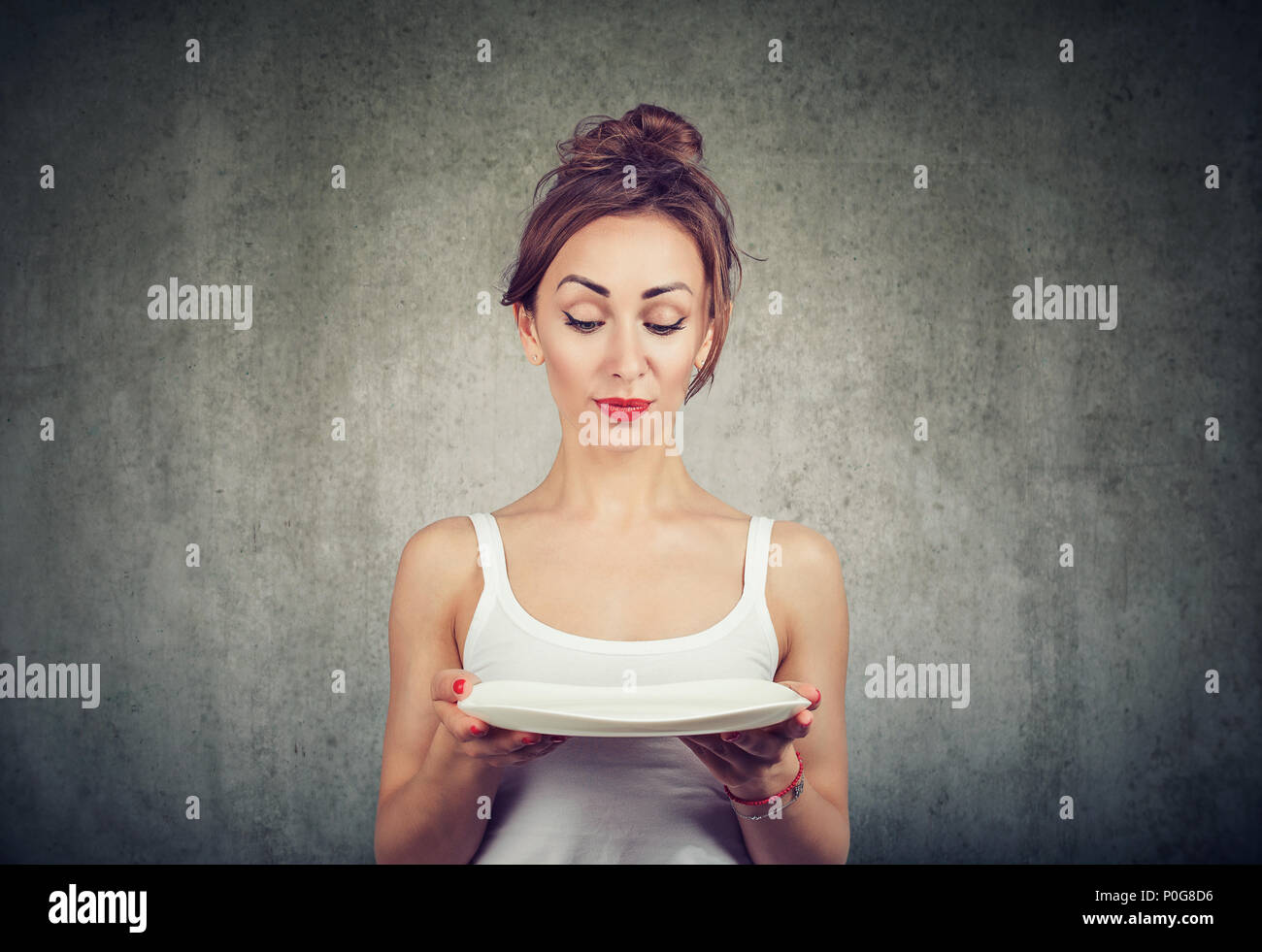 Young skinny girl holding empty plate and looking doubtful with diet restrictions standing on gray - Stock Image