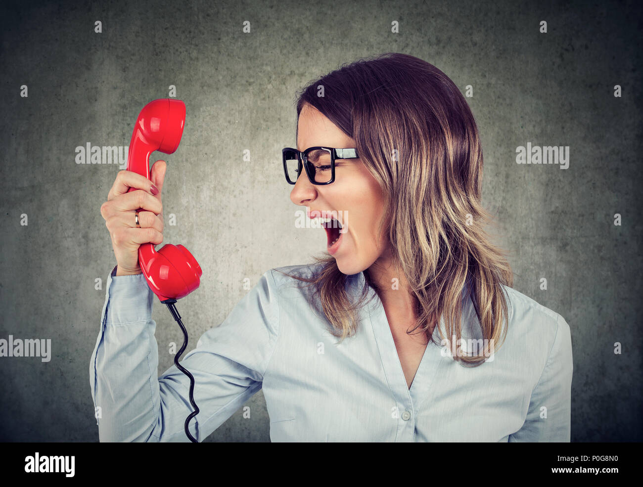 Portrait of a young angry business woman yelling at the red phone - Stock Image