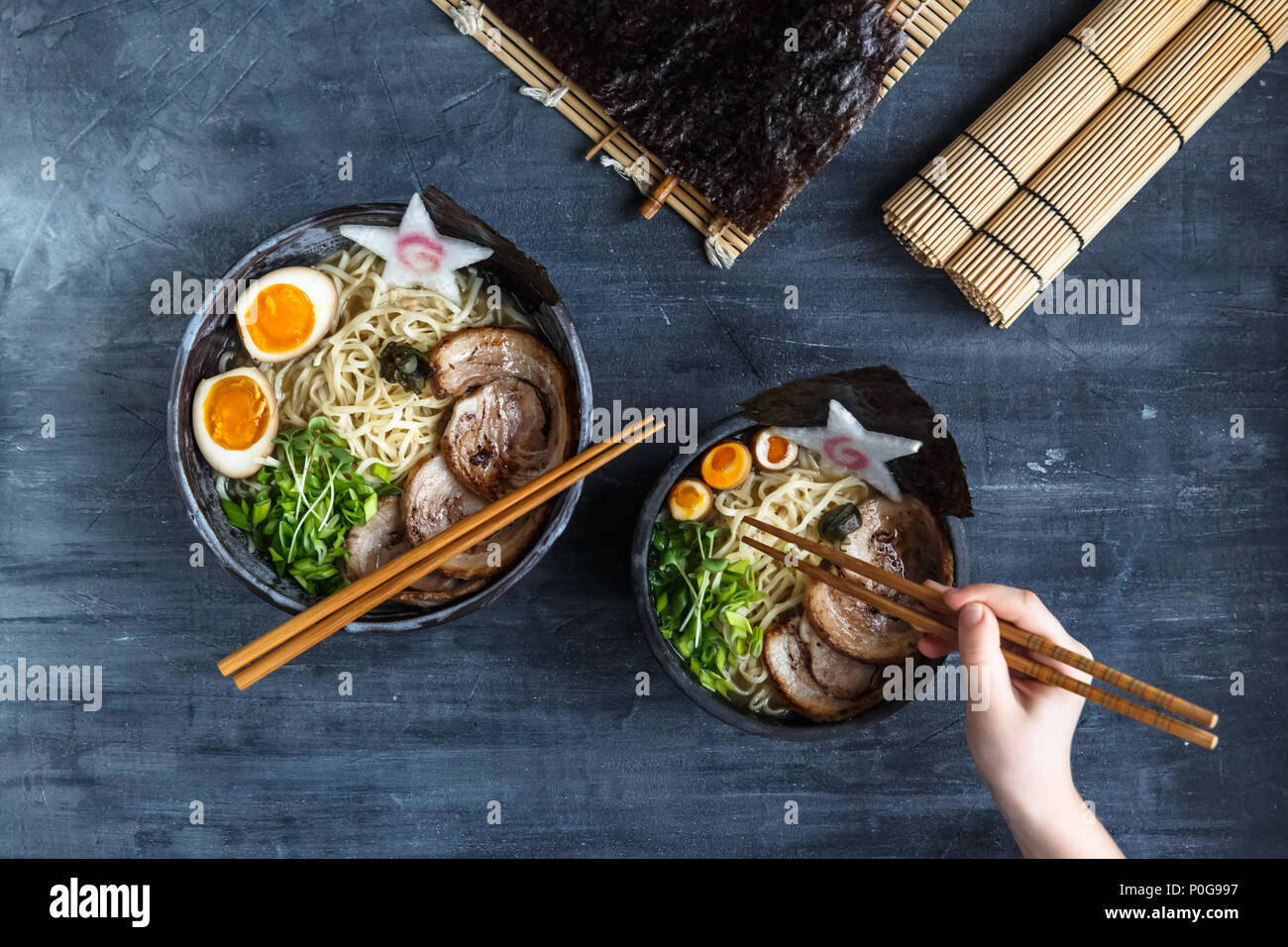 Hand with chopsticks try miso ramen - Stock Image