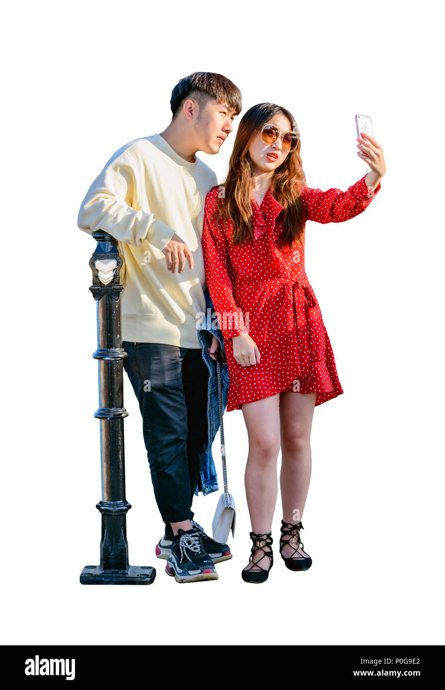 an asian oriental couple posing for a selfie on brighton pier - Stock Image
