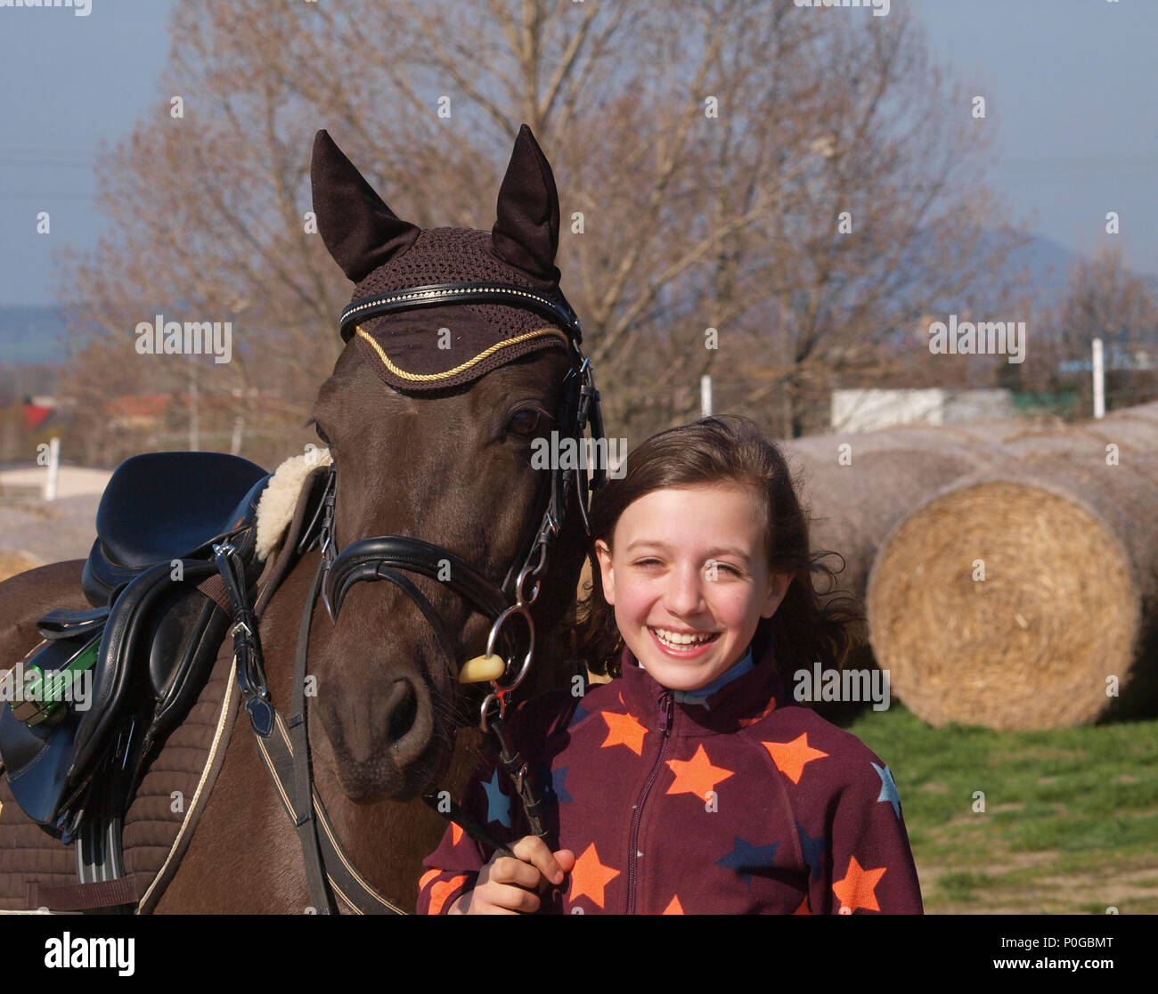 Young smilling girl with her pony before showjumping competition - Stock Image