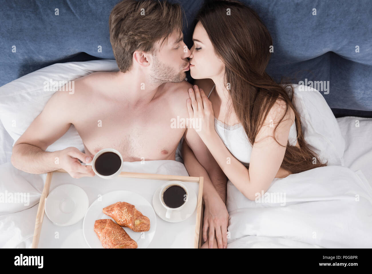 04e8cabc6e top view of young beautiful couple eating breakfast in bed and kissing -  Stock Image