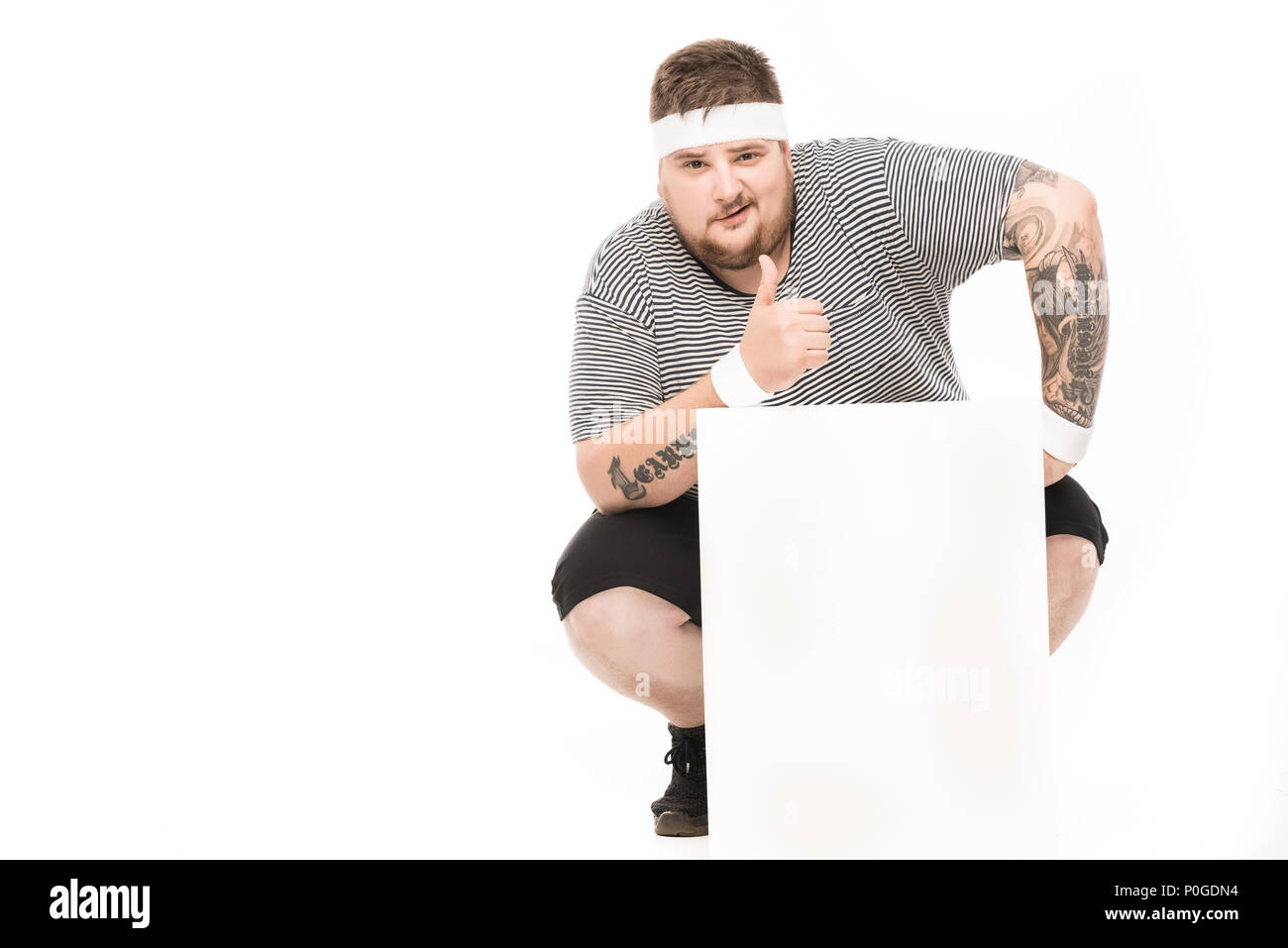 young man showing thumb up while squatting down near empty banner isolated on white - Stock Image