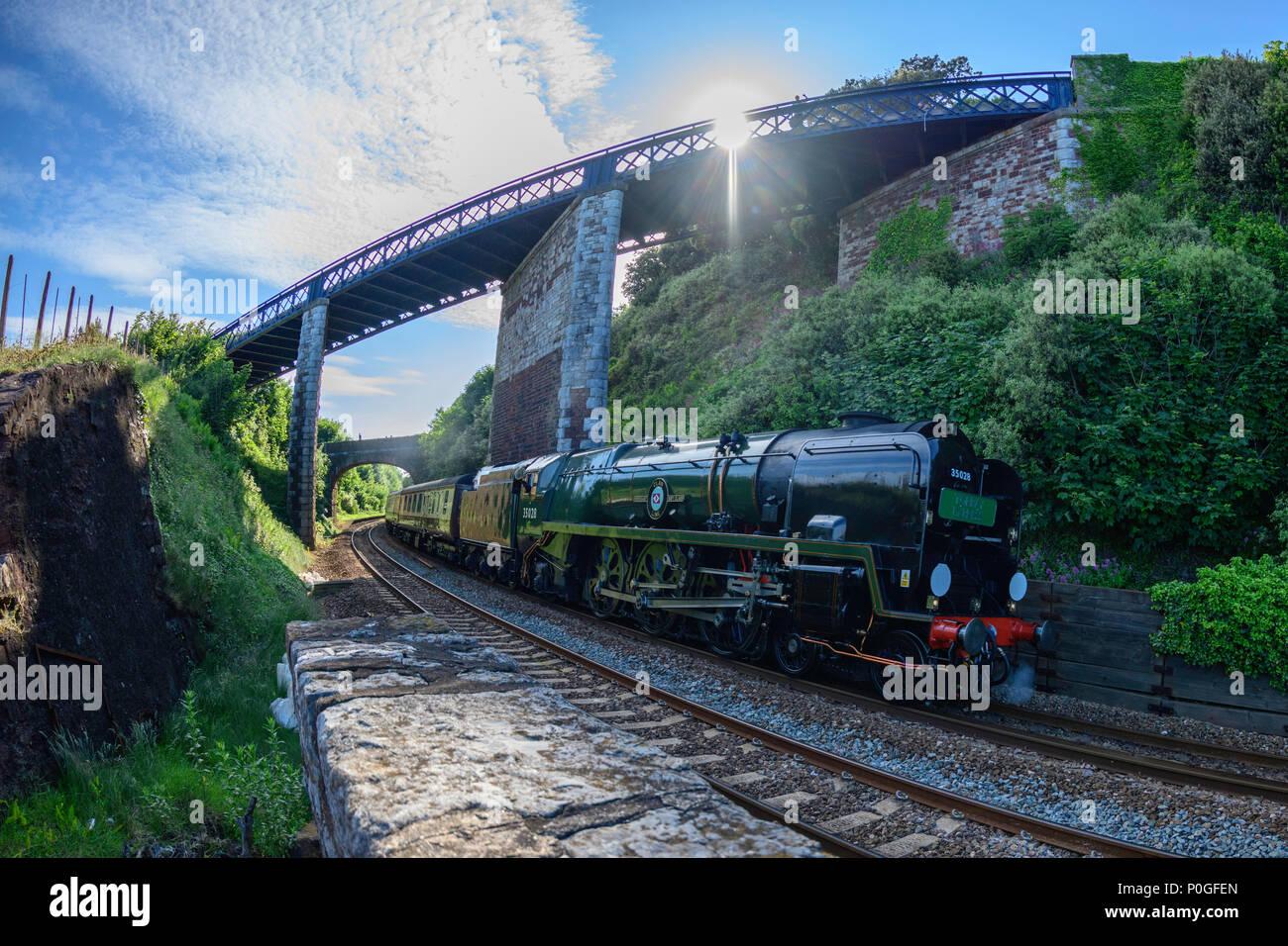 Fisheye effect photo. Steam locomotive 35028 Clan Line passes skew bridge Teignmouth south Devon UK - Stock Image