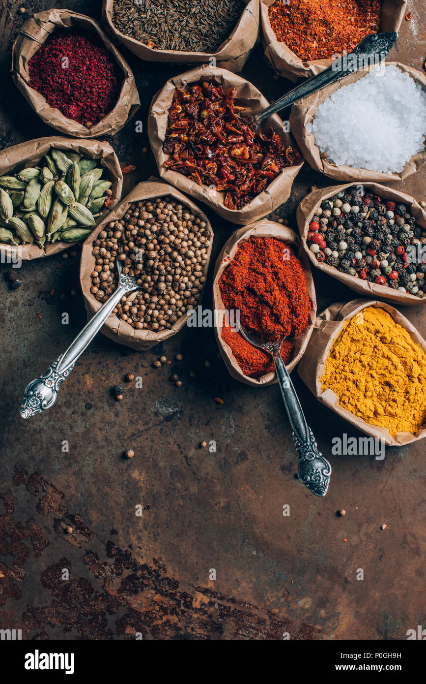 top view of colorful spices in paper bags on brown tabletop - Stock Image