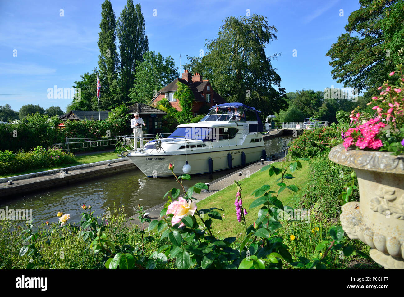 Summer plants flowering at the Sonning Lock with motorboat going through.  Sonning-on-Thames, Berkshire, UK, Great Britain - Stock Image