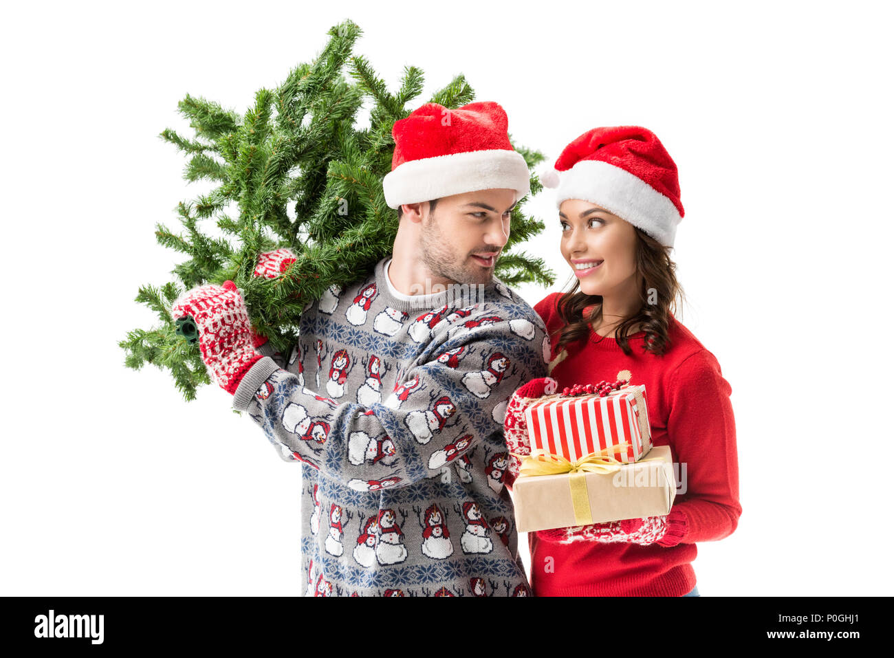 Young Couple Carrying Christmas Tree And Stack Of Gifts Isolated On White