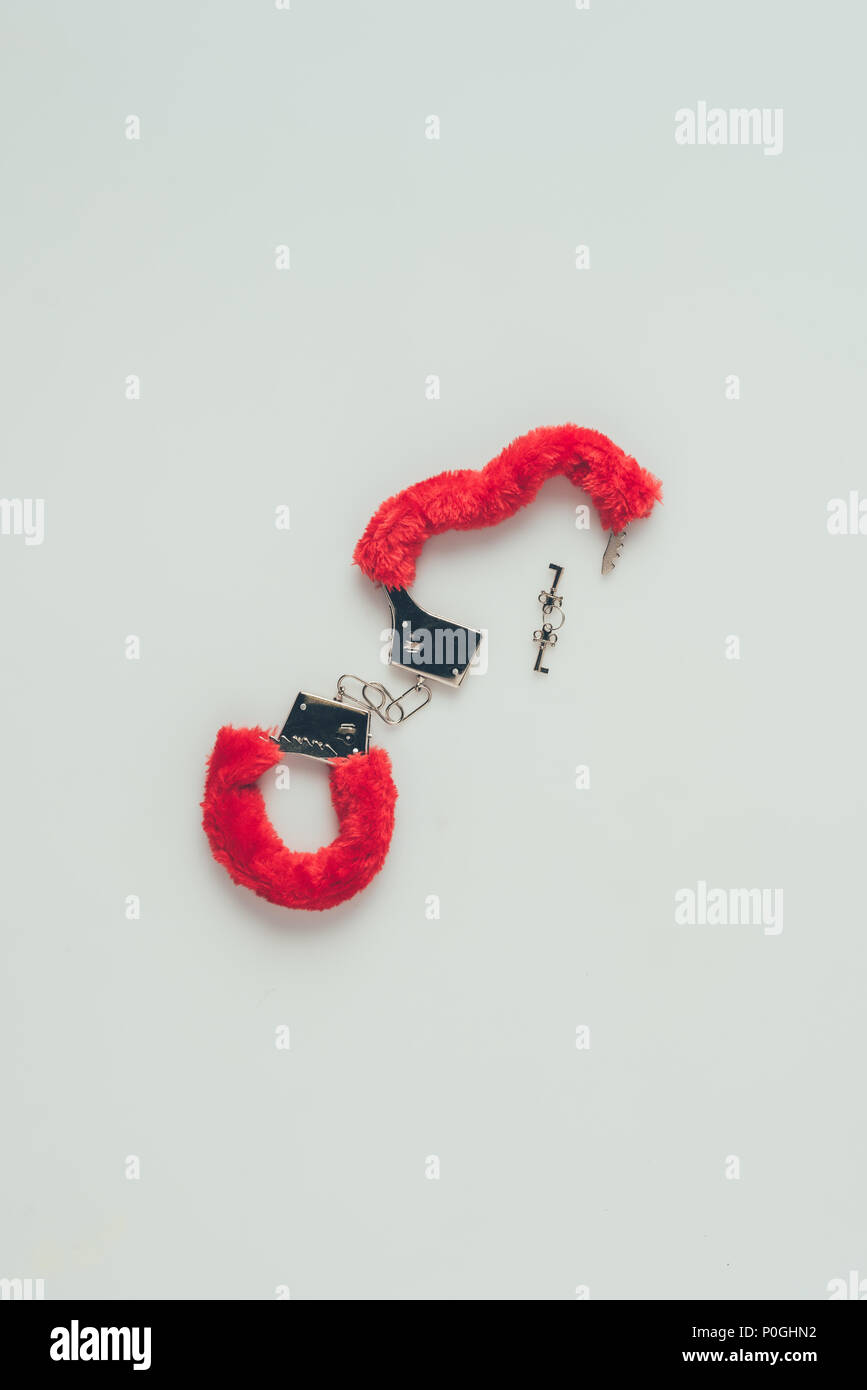 top view of red fluffy handcuffs with keys isolated on white - Stock Image