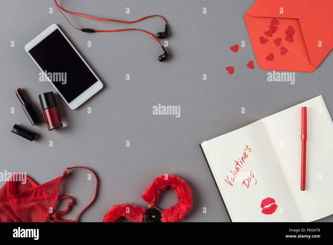 top view of smartphone, notebook with lipstick and handcuffs on gray surface - Stock Image