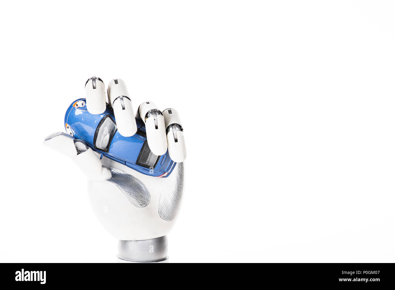 close-up view of robotic arm holding small blue car model isolated on white - Stock Image