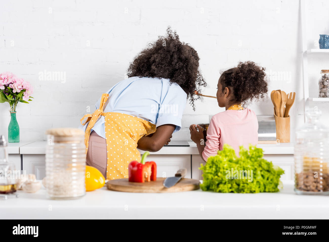 Back View Of African American Mother And Child Cooking On Kitchen