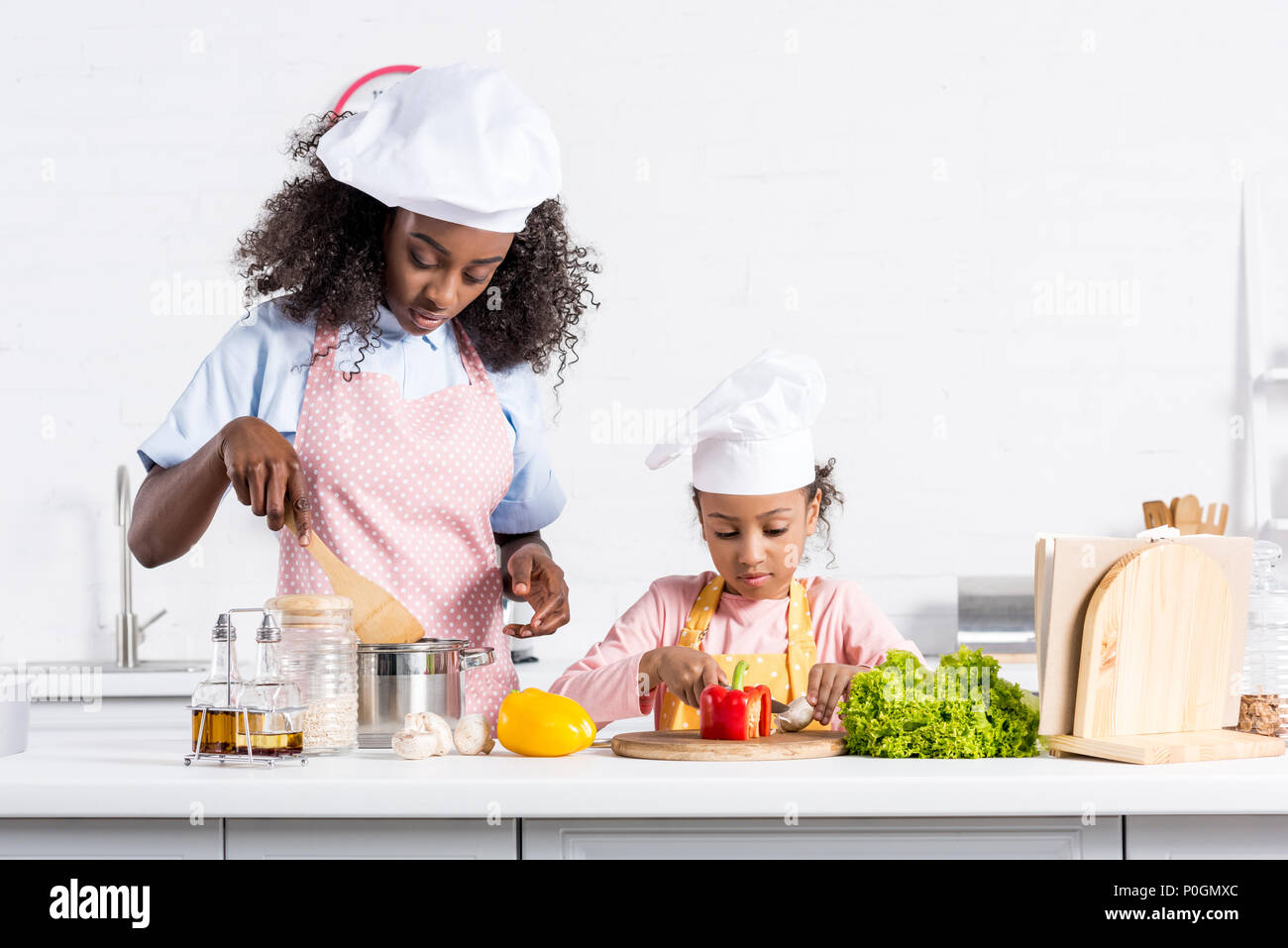 african american mother and daughter in chef hats cooking on kitchen - Stock Image