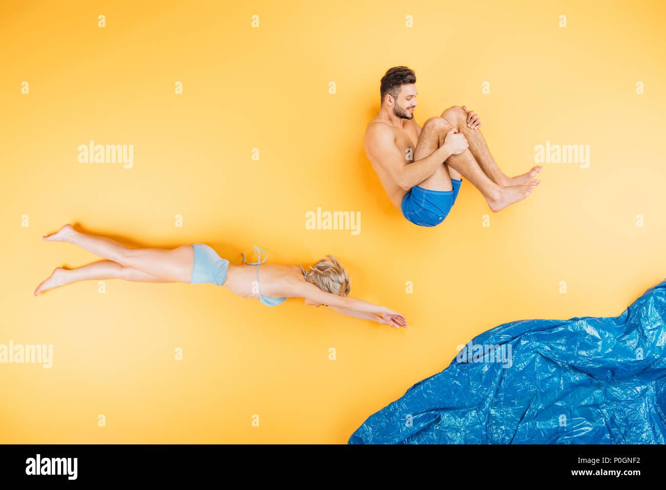 happy young couple in swimwear swimming and having fun on yellow - Stock Image