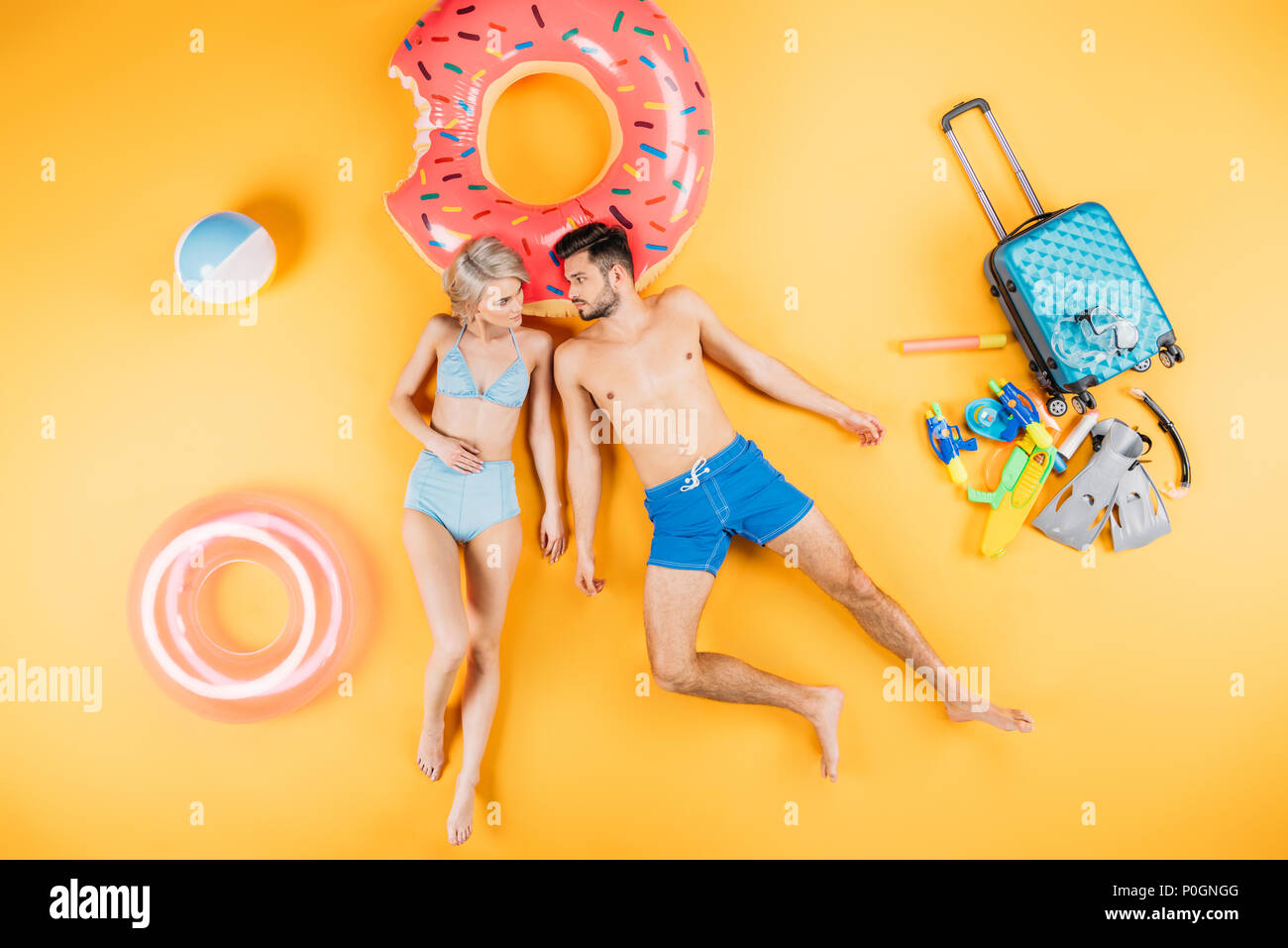 couple in swimwear looking at each other while lying with beach items and suitcase on yellow - Stock Image