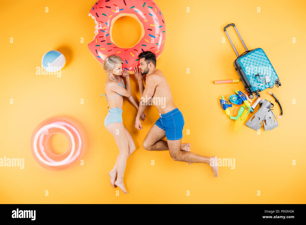 young couple in swimwear looking at each other while lying with beach items and suitcase on yellow - Stock Image