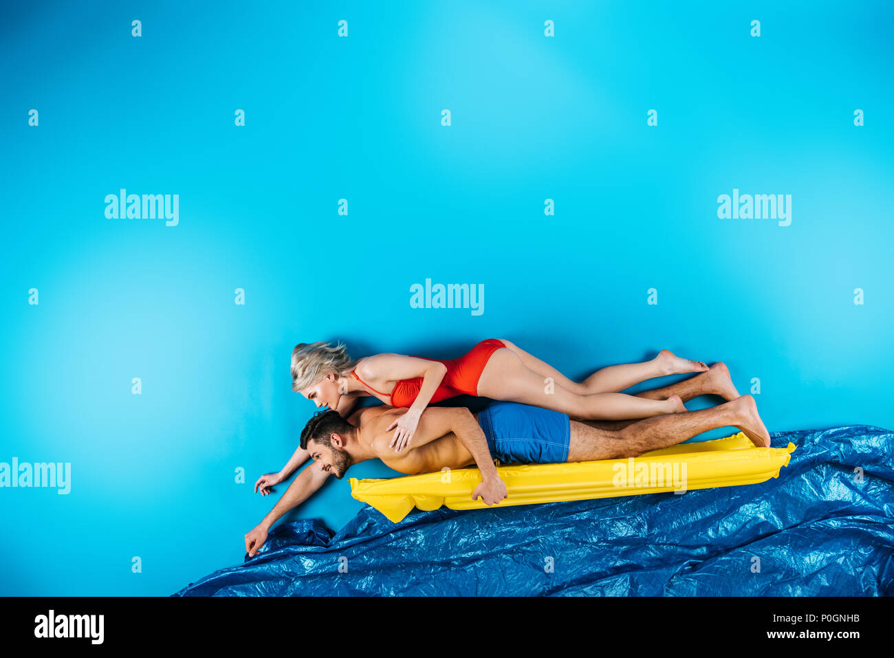 young couple in swimwear swimming on inflatable mattress on blue - Stock Image