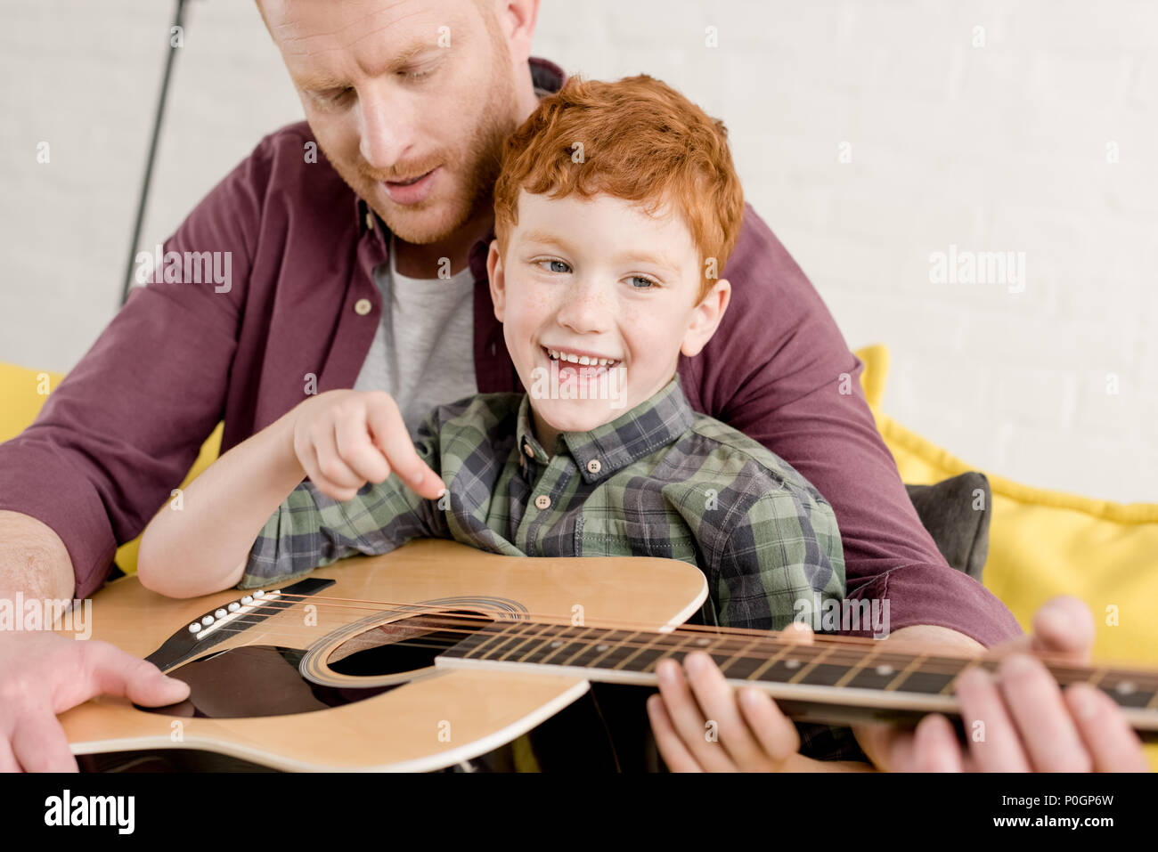 cropped shot of father teaching happy son playing guitar at home Stock Photo
