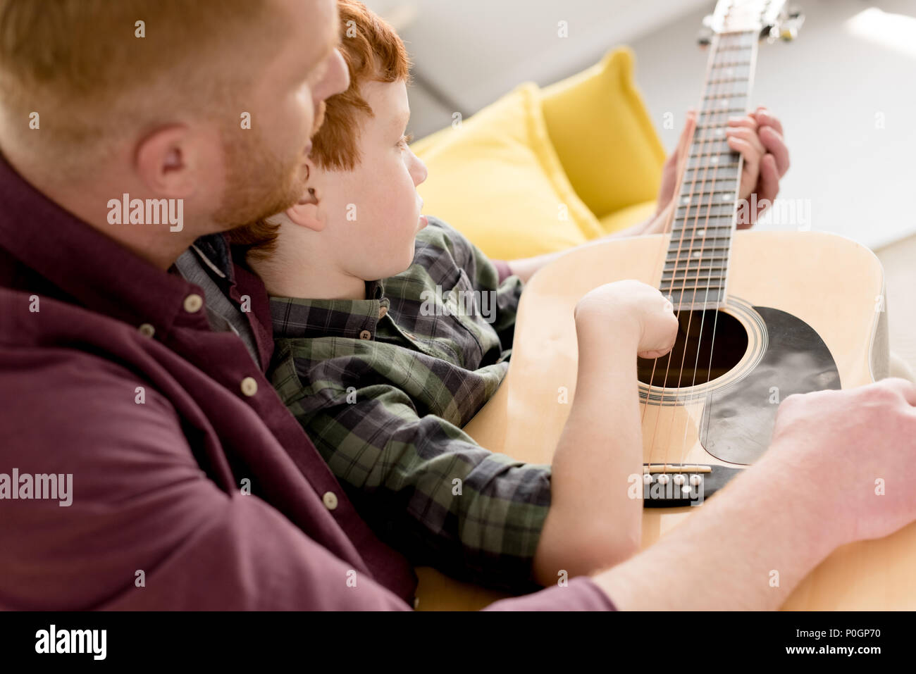 cropped shot of father teaching little son playing acoustic guitar Stock Photo