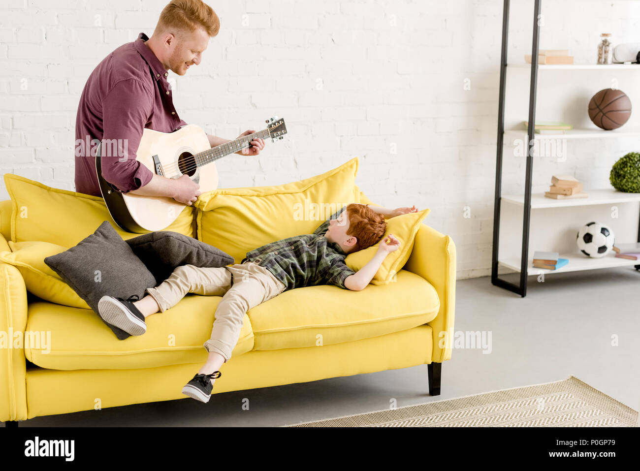 smiling father playing guitar and cute little son lying on couch Stock Photo
