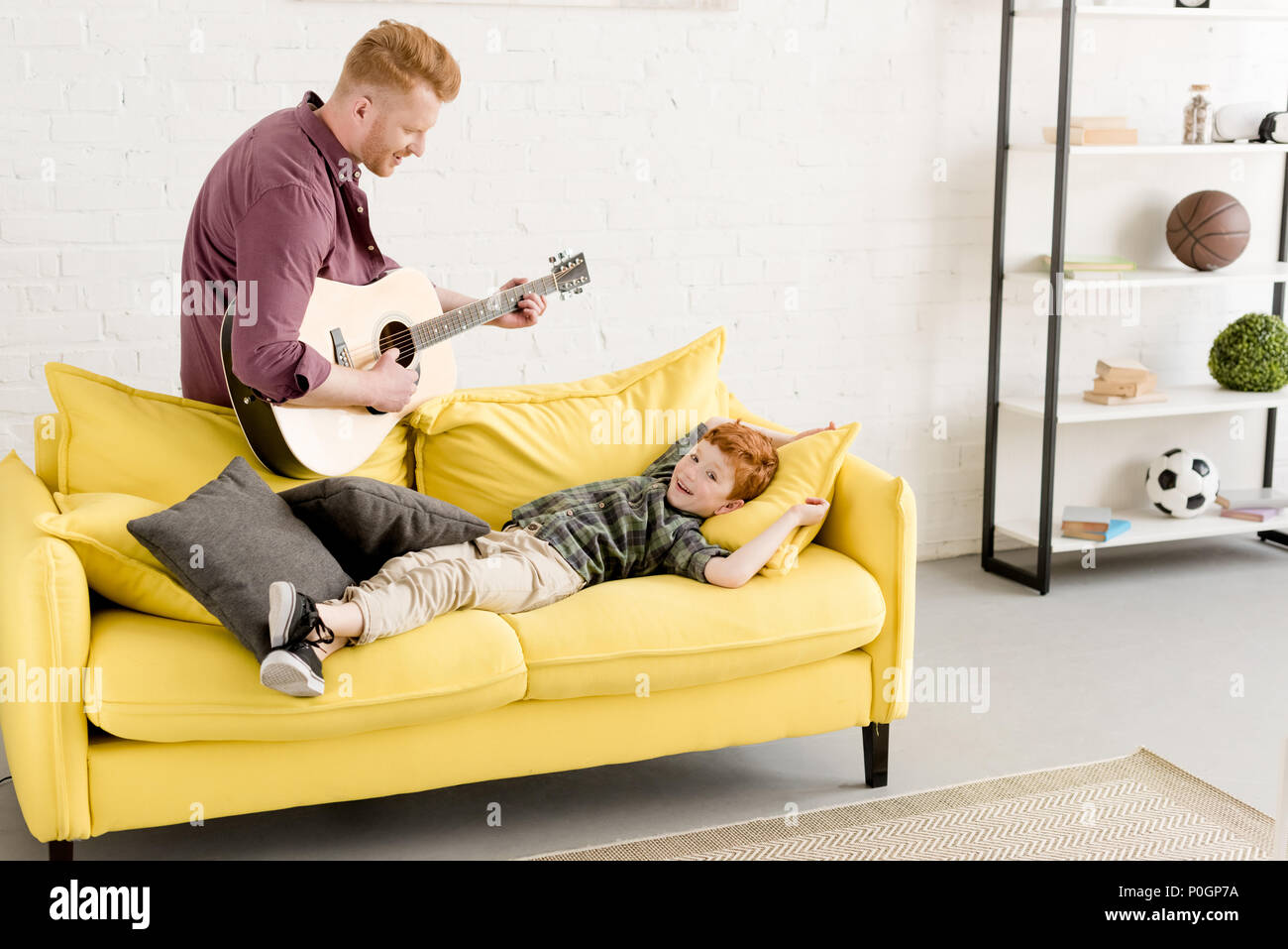 happy father playing guitar and cute smiling little son lying on couch Stock Photo