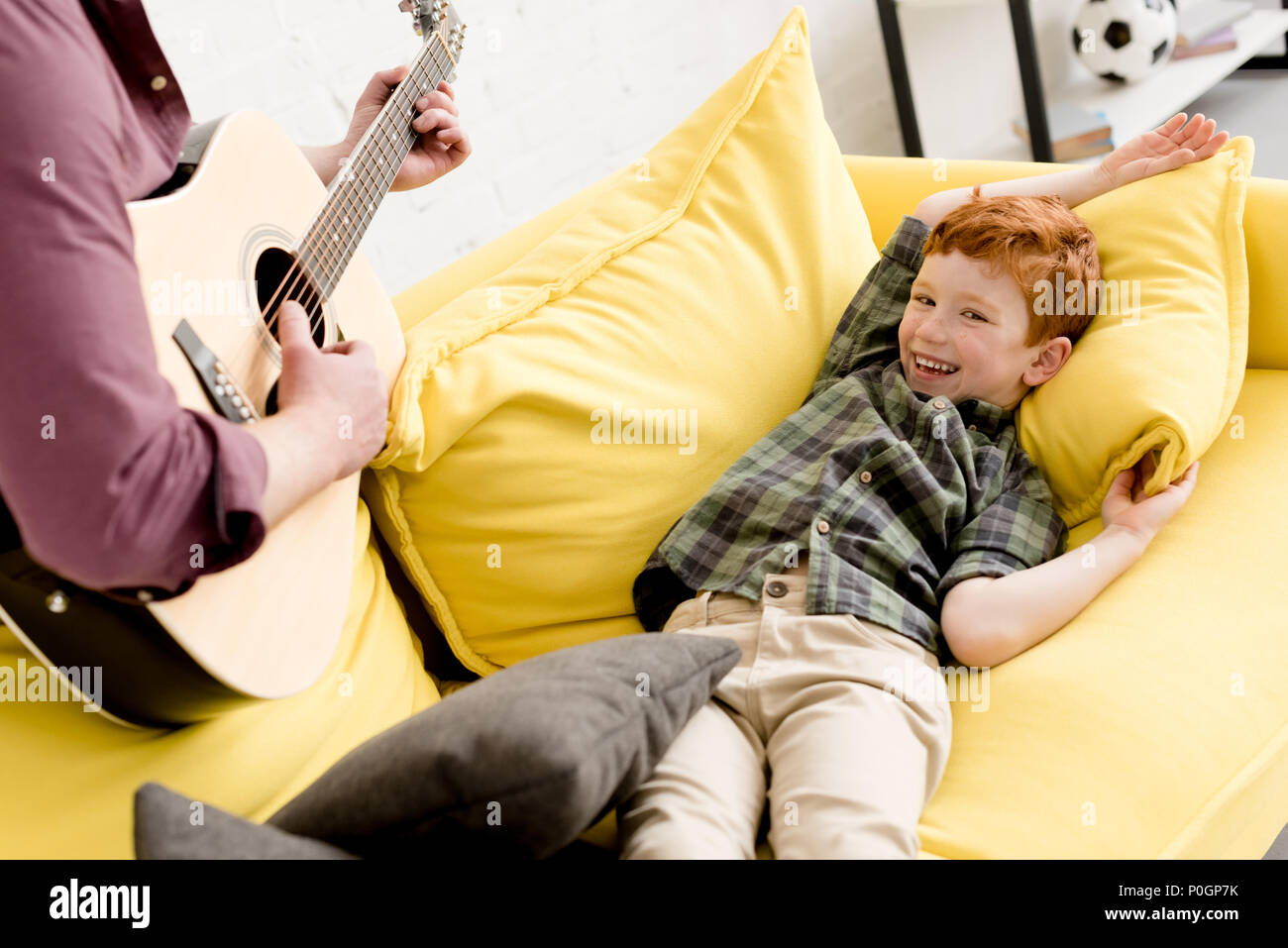 cropped shot of father playing guitar while cute happy son lying on couch Stock Photo