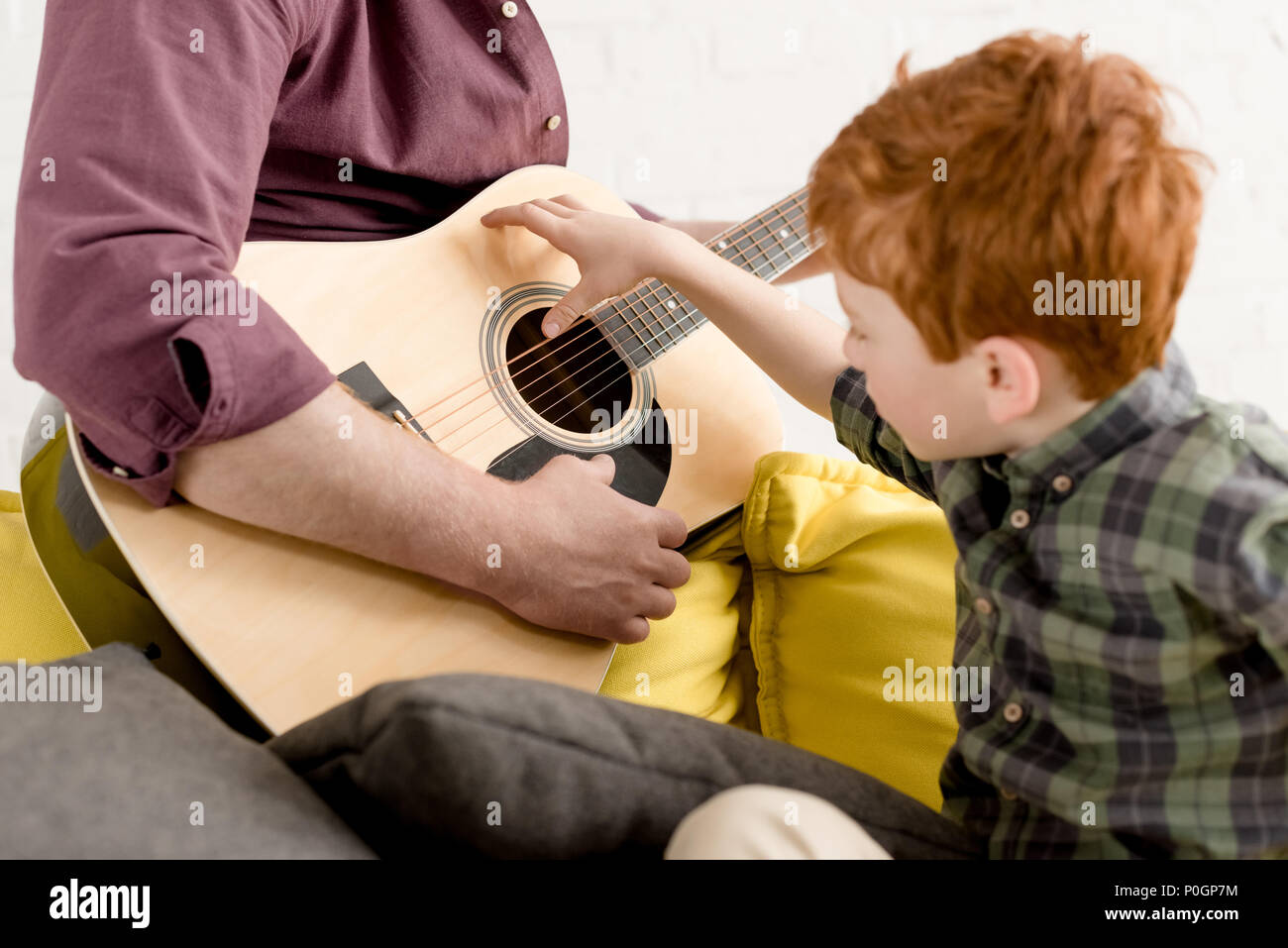 cropped shot of cute little boy looking at father playing guitar Stock Photo