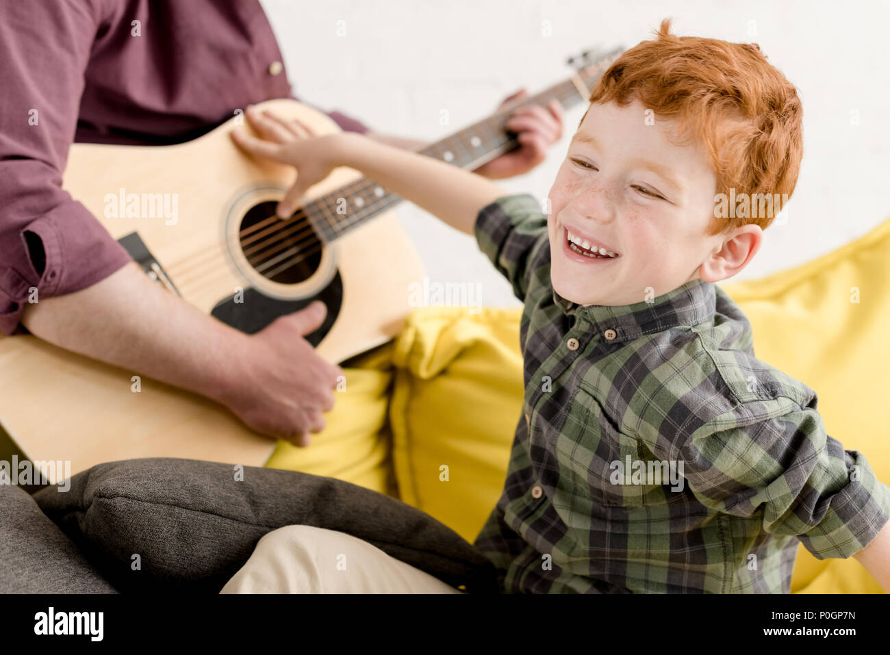 cropped shot of cute little boy laughing and father playing guitar Stock Photo