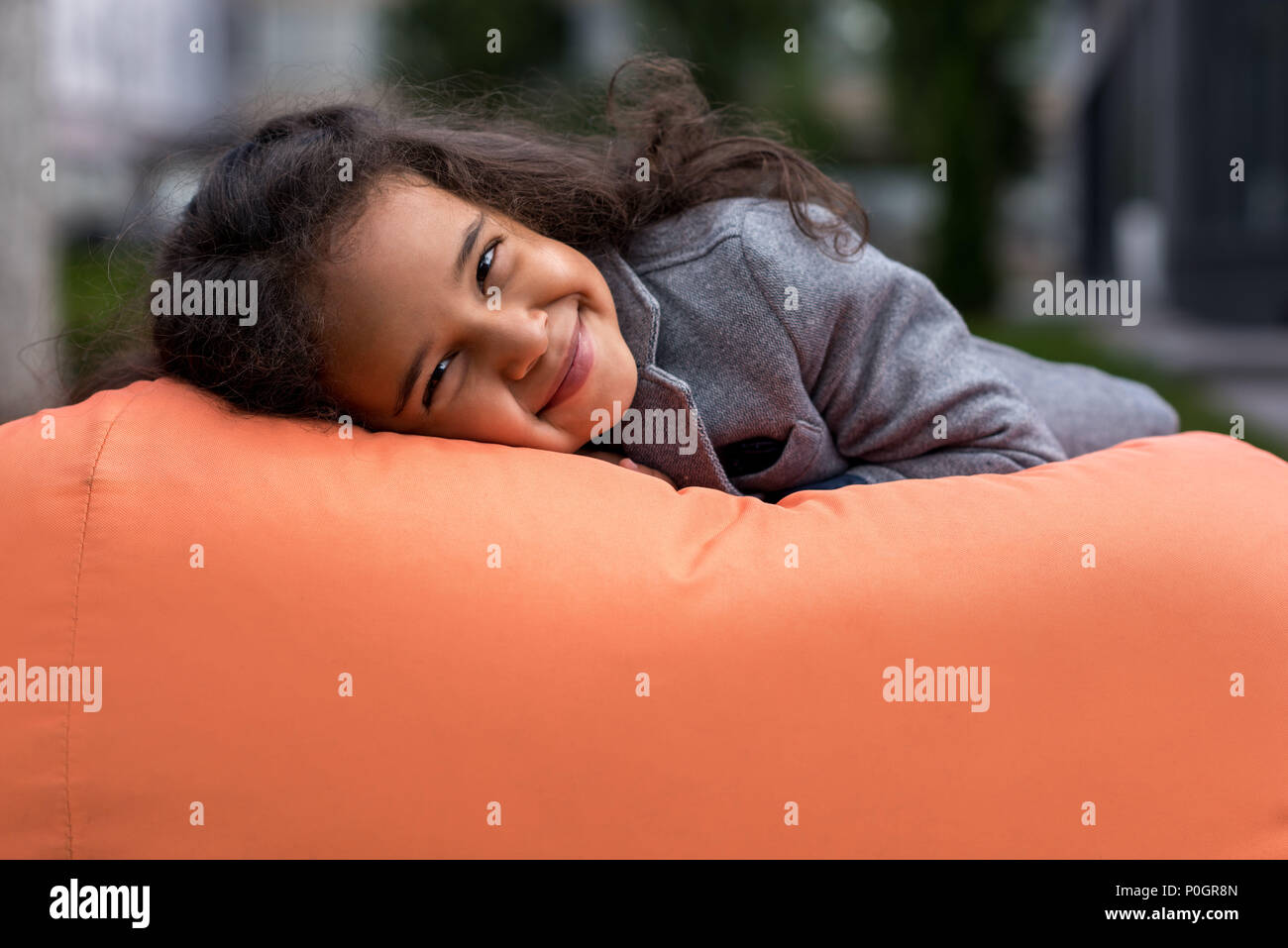 close-up portrait of beautiful african american girl lying on bean bag chair and looking at camera - Stock Image