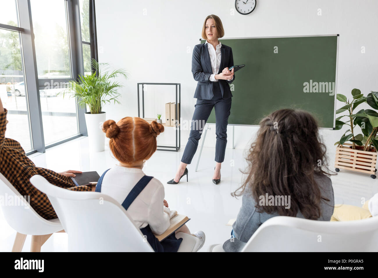 young female teacher explaining lesson to students in classroom - Stock Image