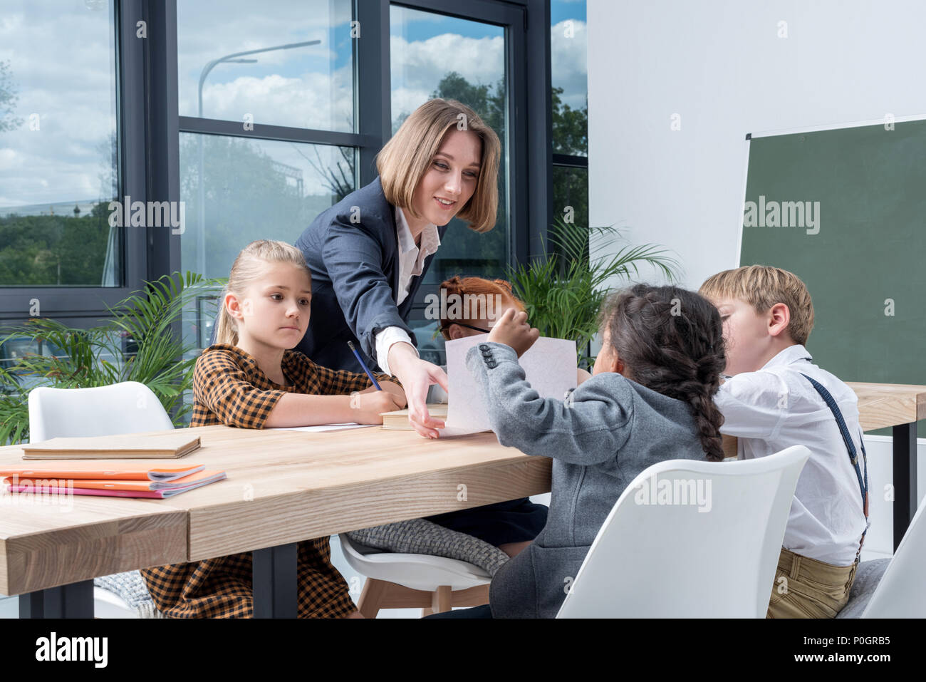 young female teacher working with cute little schoolchildren in classroom Stock Photo
