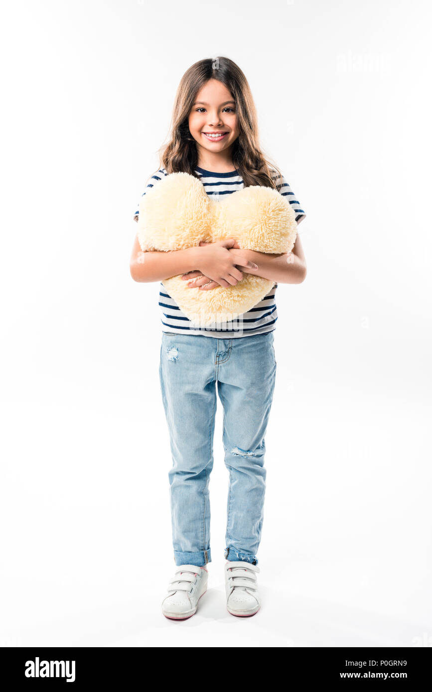 Smiling child standing and holding heart shaped pillow isolated on white - Stock Image