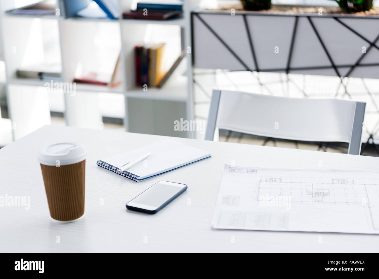 Empty workplace with blueprint, notepad, smartphone and disposable coffee cup in modern office - Stock Image