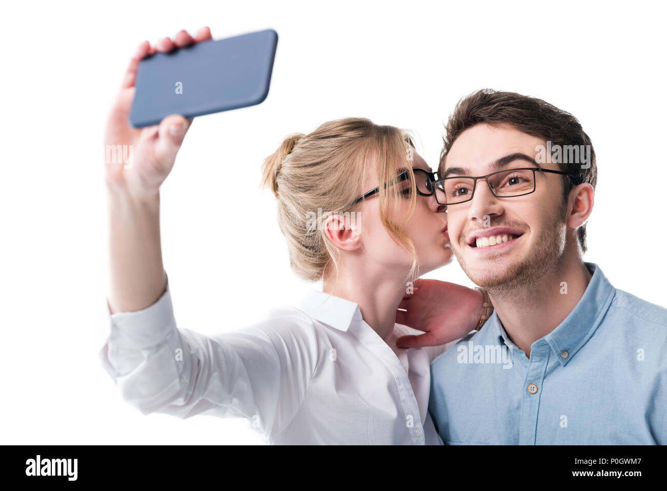 businesspeople in formal wear kissing and taking selfie on smartphone, isolated on white - Stock Image