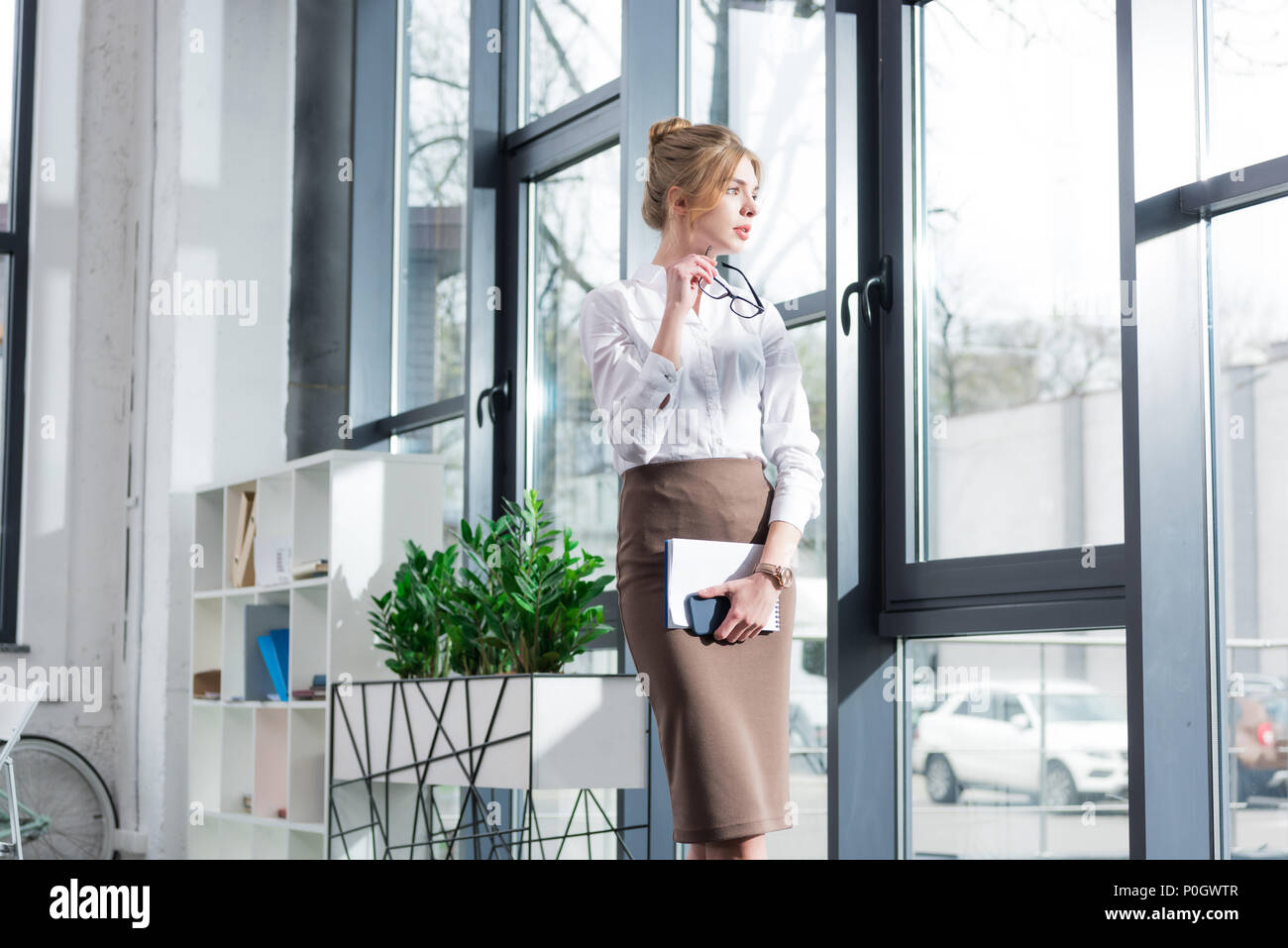 attractive blonde businesswoman in formal wear standing at window in modern office - Stock Image