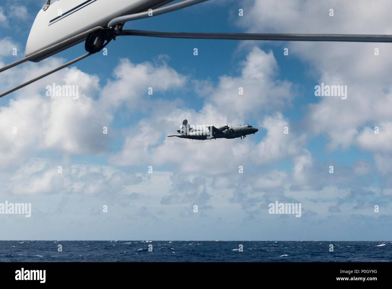 A Canadian aeroplane on a training flight flying at low level alongside a yacht sailing offshore in the North Atlantic. Stock Photo